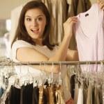 Woman holding up shirt at clothing store — Stock Photo #52037151