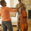 Senior African couple singing and playing upright bass — Stock Photo #52037349