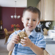 Young boy taking cookie from cookie jar — Stock Photo #52037869