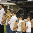 Hispanic family unloading grocery bags from car — Stock Photo #52038077