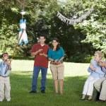 Family watching Hispanic boy hitting pinata at birthday party — Stock Photo #52038115
