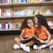 Two young sisters whispering in library — Stock Photo #52039153