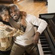 Senior African couple hugging next to piano — Stock Photo #52039207