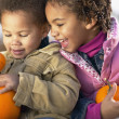 African sister and brother holding pumpkins — Stock Photo #52039627