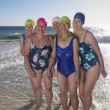 Group of senior women in bathing suits at beach — Stock Photo