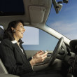 Businesswoman driving and talking on a headset — Stock Photo #52039897
