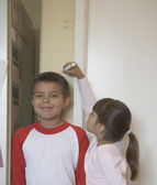 Sister measuring brother's height against wall — 图库照片