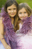 Two young girls wearing feather boa and smiling — Stock Photo