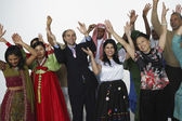 Multi-ethnic people in traditional dress cheering — Stock Photo