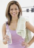 Indian woman holding water bottle and towel — Stock Photo