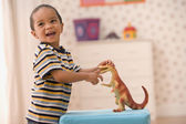Young boy playing with toy dinosaur — Photo