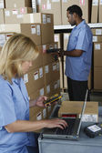 Male and female warehouse workers in warehouse — Stockfoto