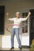Hispanic grandmother playing with hula hoops on the porch — Stock Photo