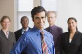 Businessman standing with coworkers in the background — Stock Photo