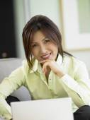 Businesswoman using a laptop on a couch — Stock Photo