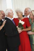 Senior man giving wife bouquet of flowers while friends watch — Stock Photo