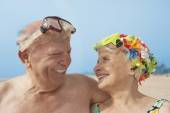 Senior couple smiling at each other at beach — Stock Photo