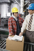 Man and woman talking in warehouse — Stock Photo
