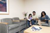 Family reading magazines in waiting room — Stock Photo
