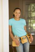 African woman wearing tool belt — Stock Photo