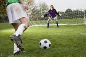 Girl kicking soccer ball toward goal — Stock Photo