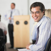 Businessman smiling in conference — Stock Photo