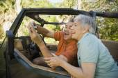 Senior Hispanic couple taking self-portrait with jeep — Stock Photo