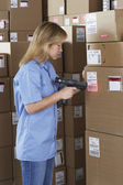 Female warehouse worker scanning package — Stock Photo