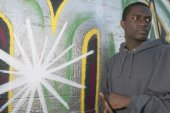 Young African man leaning on graffitied wall — Stock Photo