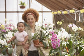 African American mother with baby in greenhouse — Stock Photo