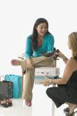 Sales clerk assisting teen girl buying shoes — Stock Photo
