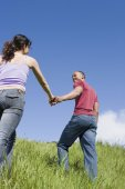 Couple holding hands and walking up hill — Stock Photo
