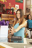 Hispanic woman looking at jewelry in boutique — Foto Stock