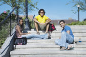 Multi-ethnic college students sitting on steps — Stock Photo