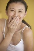 Mulher asiática, cobrindo a boca e rindo — Fotografia Stock