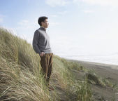Asian man standing on the dunes — Stock Photo