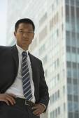 Asian businessman in front of sky scraper — Stock Photo