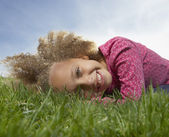 Young girl smiling for the camera in the grass — Stock Photo