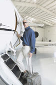 Man with suitcase boarding airplane in hanger — Stock Photo