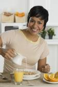 Hispanic woman pouring milk on cereal — Stock Photo