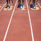 Female track athletes at starting line — Stock Photo