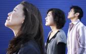 Three Asian people looking up — Stock Photo
