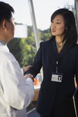 Asian businesswoman shaking hands with doctor — Stock Photo