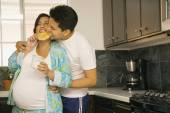 Enceinte couple en pyjama dans la cuisine — Photo