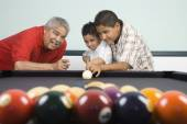 Hispanic grandfather teaching grandsons to play pool — Stock Photo