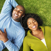 African couple listening to same mp3 player — Stock Photo