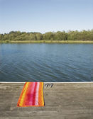 Towel and flip-flops by lake — Foto Stock