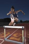 Female track athlete clears a hurdle — Stock Photo