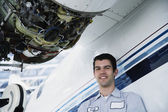 Middle Eastern repairman next to airplane engine — Stock Photo