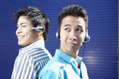 Two young men back to back wearing headsets — Stock Photo